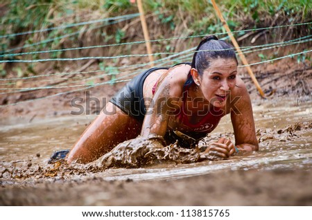DALLAS, TEXAS - SEPTEMBER 15: Unidentified female participant crawls under the wires at a mud pit in the Dash of the Titans Mud Run Race on September 15, 2012 in Dallas, Texas.