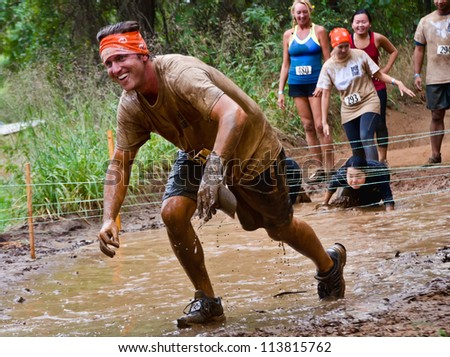 DALLAS, TEXAS - SEPTEMBER 15: Unidentified male participant passes through a mud pit in the Dash of the Titans Mud Run Race on September 15, 2012 in Dallas, Texas.