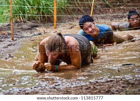 DALLAS, TEXAS - SEPTEMBER 15: Unidentified participants crawl through a mud pit in the Dash of the Titans Mud Run Race on September 15, 2012 in Dallas, Texas.