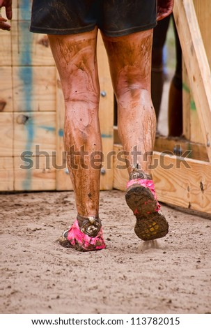DALLAS, TEXAS - SEPTEMBER 15: Unidentified race participant approaches wall obstacle in the Dash of the Titans Mud Run Race on September 15, 2012 in Dallas, Texas. Closeup of the runner's muddy legs.