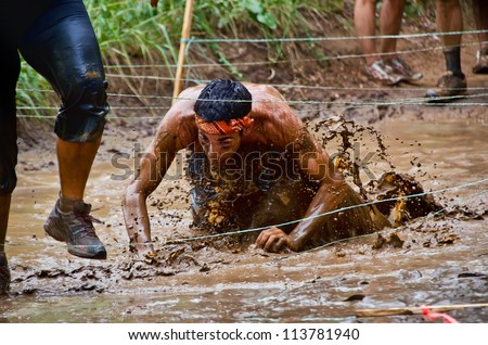 DALLAS, TEXAS - SEPTEMBER 15: Unidentified race participant crawls through a mud pit in the Dash of the Titans Mud Run Race on September 15, 2012 in Dallas, Texas.