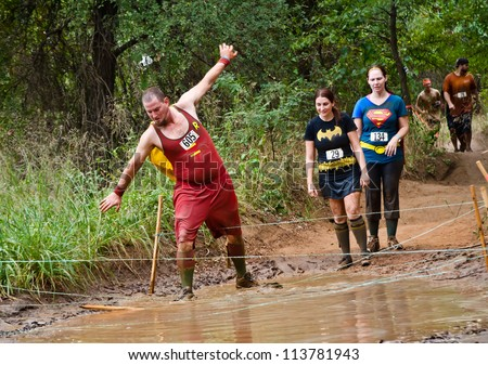 DALLAS, TEXAS - SEPTEMBER 15: Unidentified race participants are dressed up in funny costumes at the mud pit in the Dash of the Titans Mud Run Race on September 15, 2012 in Dallas, Texas.