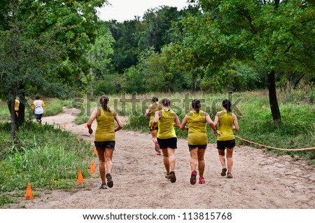DALLAS, TEXAS - SEPTEMBER 15: Unidentified team participants run along the course near finish in the Dash of the Titans Mud Run Race on September 15, 2012 in Dallas, Texas.