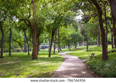 Dallas Texas. Turtle Creek Park. Downtown City Park with a sidewalk path and empty bench