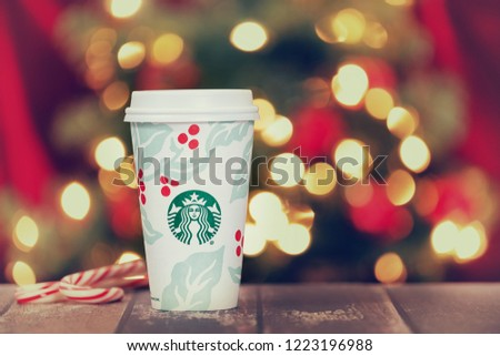 Dallas, TX - November 5, 2018: Starbucks popular holiday beverage, served in the new 2018 designed holiday cup. Displayed on rustic table with candy canes. Festive Christmas lights background. #1223196988