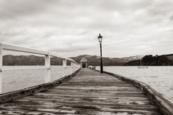 Daly's Wharf or Akaroa jetty in Akaroa Harbor old wooden pier with shed and orange round conical roof at end vintage style sepia toned image.