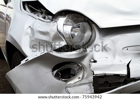 Damage to the front of a white car after an accident.