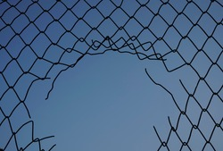 damage wire mesh on blue sky  background. Mesh netting with hole isolated on blue  background