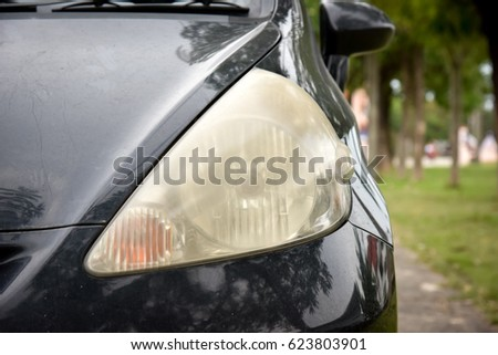 Damaged and blurred headlight surface as a result of weather condition and aging of a car #623803901