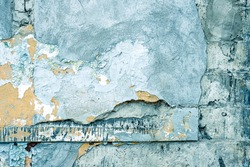Damaged blue wall texture background. Creative backdrop. Old, closed factory building wall fragment. Weathered and cracked bricks with concrete and peeled off blue paint. Close up, copy space