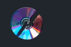 Damaged CD, DVD compact disc. Data destruction. Broken CD and DVD disc isolated on black background, space for text