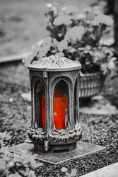 damaged grave light with  candle on a grave