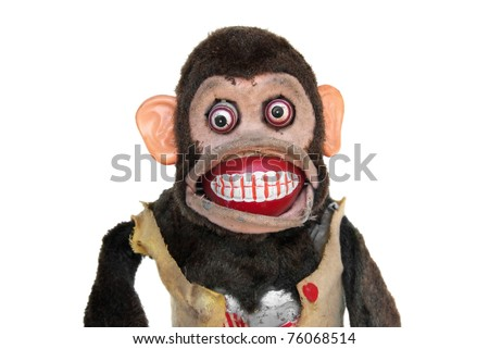 Damaged mechanical chimp with ripped vest, uneven eyes