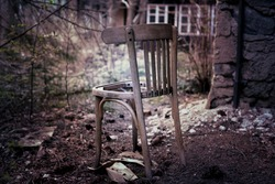 Damaged old chair beside the abandoned building