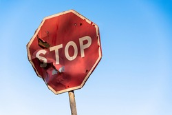Damaged road sign stop covered with scratches and rusty. Rumpled road sign on a blue sky background. Stop sign with partly bent surface. Urban Grunge Background