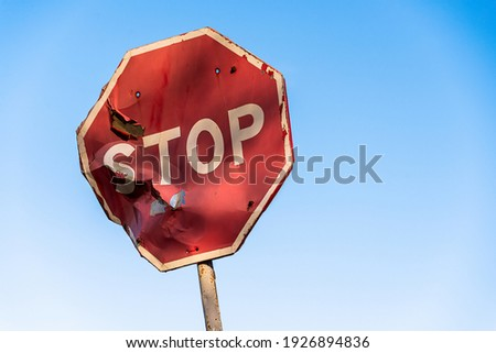 Damaged road sign stop covered with scratches and rusty. Rumpled road sign on a blue sky background. Stop sign with partly bent surface. Urban Grunge Background Stockfoto ©