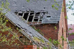 Damaged slate roof tiles on a pitched roof on a derelict house