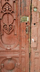 Damaged surface of old painted wooden door with ornate grating fragment and retro lock of intercom keyboard. Grunge details of dilapidated building entrance in European city