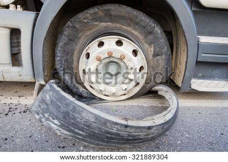 Damaged 18 wheeler semi truck burst tires by highway street.