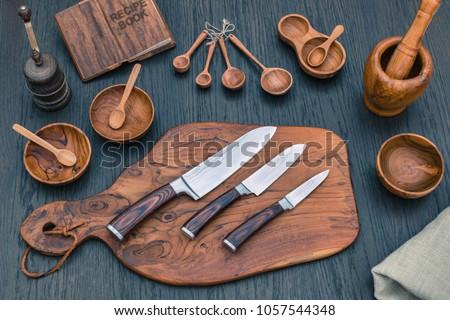 Damascus kitchen steel Knives, Wooden kitchen cutting Board, wooden kitchen measuring spoons,   Recipe Book. Kitchen Utensils background with Santoku damascus steel blade knife