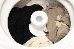 Damp pants and towels in an open washing machine after being washed ready for the dryer. Open top loading washing machine with its lid open and laundry finished.