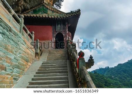 Photo of  Danan Rock scenic spot. Temple with burning dragon head incense in Liangyi, Nanyan Palace. Wudang Mountain, Hubei province, China (text: Liangyi building)