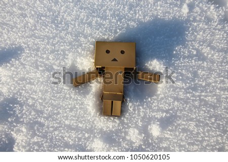 Stock Photo Danbo figure making a snow angel.