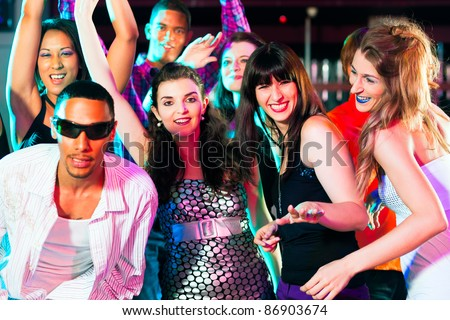 Dance action in a disco club - group of people, men and women of different ethnicity, dancing to the music having lots of fun