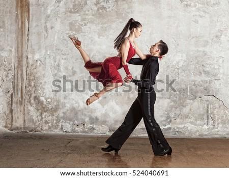 Dance beautiful couple dancing ballroom dancing on wall background. Toned image #524040691