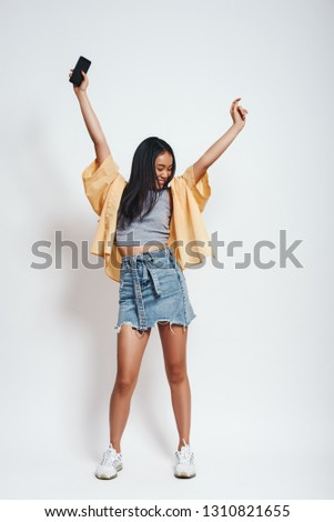 Dance, dance, dance! Full length portrait of pretty asian woman in casual wear holding smartphone in one hand, dancing and looking away. Grey background. #1310821655