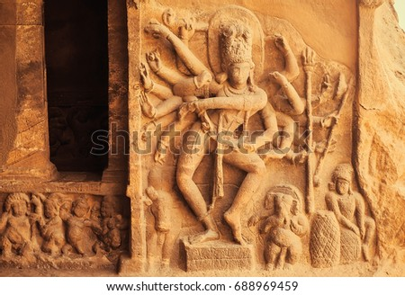Dance of Shiva Lord with many hands. Entrance to the Hindu temple with 6th century reliefs. Ancient Indian architecture in Karnataka, India.