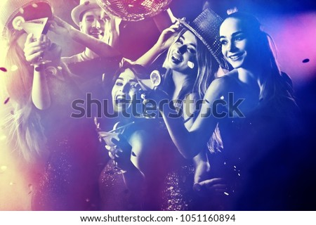 Dance party group people dancing. Women and men have fun in night club. Rest after hard day at work. Back light on girls hair. People dance under influence of alcohol. Toning and blur for background.