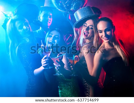 Dance party with group people dancing . Women and men have fun and drinking martini cocktail in night club. Girl on foreground and disco ball color illumination background. Rest after hard day\'s work.