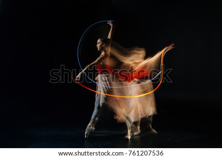 Dance studio. Serious well built female dancer standing against black background and practicing her movements while visiting dance studio #761207536