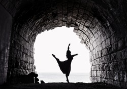 Dancer, graceful woman dancing in the arch, ballet dancer. ballerina dancing in the old fortification place. Contrast, silhouette of girl figure on sunny day. Woman figure. Black and white photo