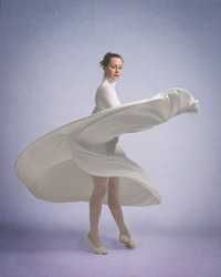 Dancer in a white dress twirls around as the skirt flutters with the movement
