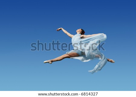 Dancer jumping against blue sky wearing blue