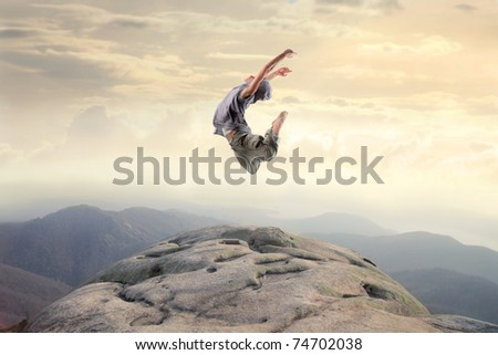 Dancer jumping on a rock