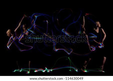 Dancer light painting abstract colorful swirls on black background