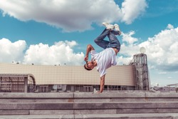 dancer on one arm dances break dance, hip-hop, artist acrobat. Summer city, clouds background. Active youth lifestyle, young male dancer, fitness movement workout breakdancer. Free space for text