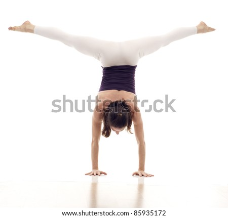 Dancer standing on hands, holding legs in air isolated  over white background