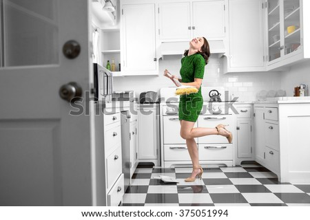Dancing and singing while cleaning sweeping kitchen floor fun spirited joyful attitude chores