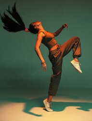 Dancing athletic mixed race girl performing expressive fiery hip hop or ethnic modern dance in colourful studio light