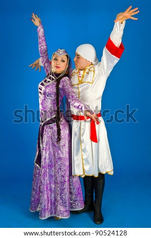 Dancing boy and girl in traditional costume of Georgia on blue background
