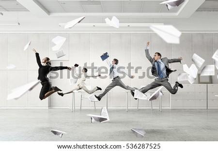 Shutterstock Dancing businesspeople in office room . Mixed media