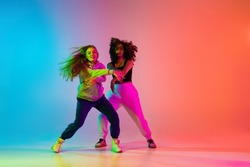 Dancing connect. Portrait of two young beautiful hip-hop girls dancing on colorful gradient blue orange at dance hall in neon. Youth culture, movement, active lifestyle, action, street dance, ad