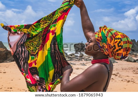 Dancing Ghana woman on the beautiful beach of Axim, located in Ghana West Africa. Headdress in traditional colors from Africa.