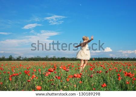 Stock Photo dancing girl in poppy field under blue sky