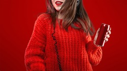 Dancing Girl with Headphones Listening Music dancing and drinking cola from the red can on Red Background. Stylish fashionable young cool girl enjoy the dj party.