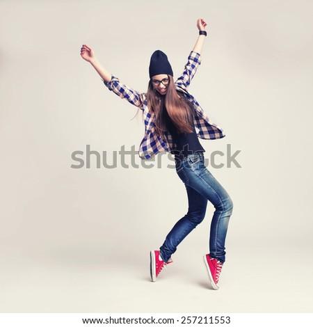 Shutterstock Dancing hipster girl in glasses and black beanie on light background